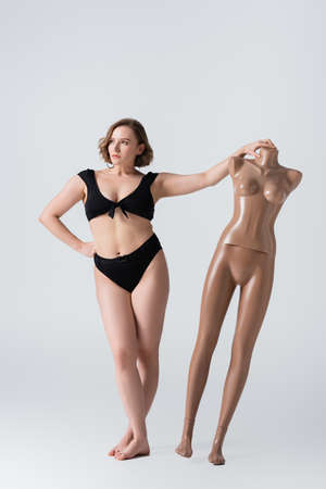 full length of overweight and barefoot young woman posing with plastic mannequin on white Foto de archivo