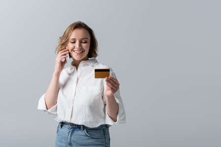 partial view of plus size woman holding credit card and talking on smartphone isolated on gray Stockfoto