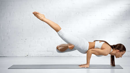 Side view of woman balancing on hands while practicing yoga near white wall