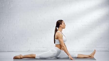 Young woman doing split on yoga mat Imagens
