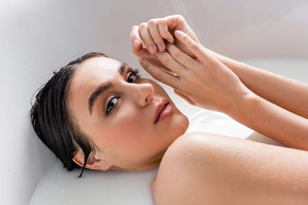 pretty woman holding hands near face while relaxing in bath with milk Stock fotó