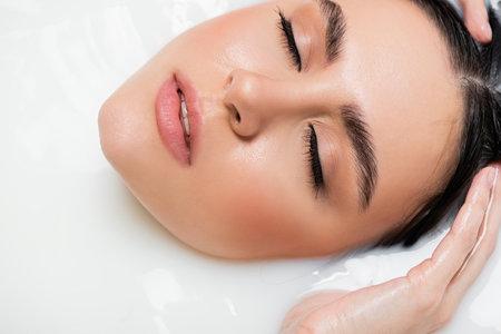 close up view of female face in milk bath