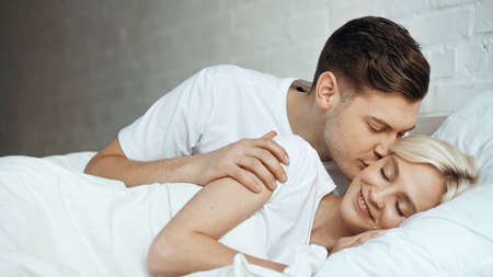 happy man kissing blonde woman lying with closed eyes in bed