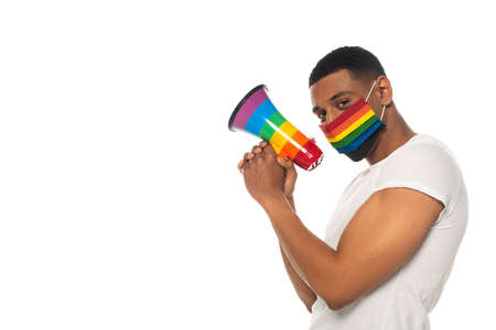 african american man with medical mask and megaphone in colors looking at camera isolated on white Reklamní fotografie