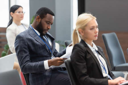 African american businessman looking at documents during business training Standard-Bild