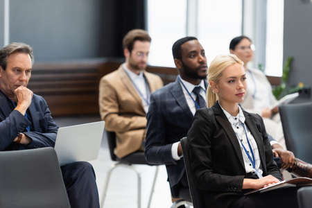 Businesswoman with paper folder sitting in conference room near interracial colleagues Stockfoto