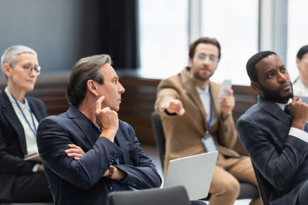 Mature businessman with laptop sitting near multiethnic colleagues in conference room during seminar