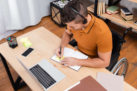overhead view of handicapped man in headset writing on notebook