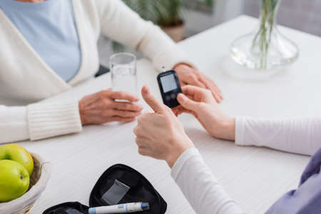 cropped view of social worker showing thumb up near glucometer and senior diabetic woman
