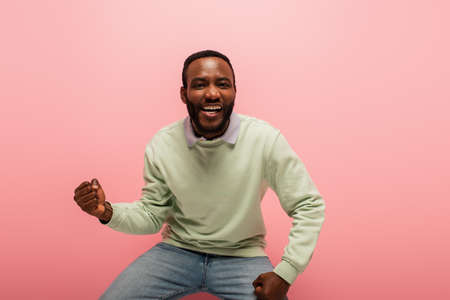Smiling african american man showing yes gesture isolated on pink