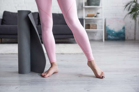 cropped view of barefoot woman in leggings standing near yoga mat at home