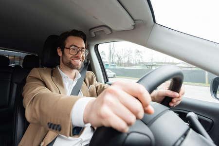 smiling bearded man in glasses driving modern car Standard-Bild