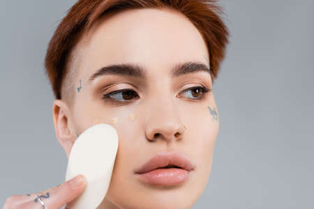 close up of tattooed woman applying makeup foundation on face with sponge isolated on gray