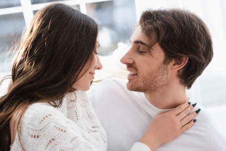 Side view of smiling woman hugging boyfriend at home