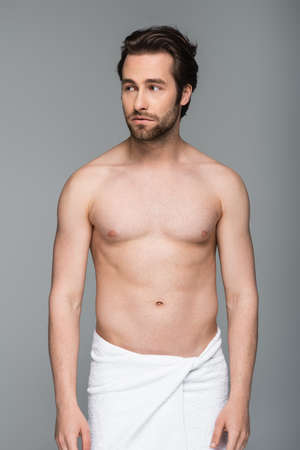 young muscular man in towel looking away isolated on gray Reklamní fotografie