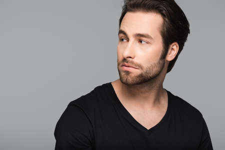 bearded and good-looking man in black t-shirt looking away isolated on gray Banque d'images