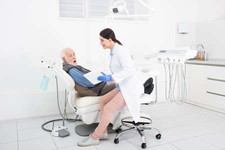 amazed senior patient lying in dental chair and taking consultation from doctor with tablet in hands