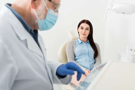 positive woman sitting in dental chair and looking at dentist standing near equipment in clinic
