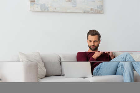 man with cup of coffee sitting on sofa near laptop