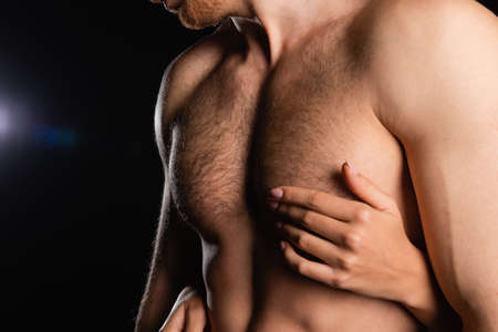 partial view of female hands touching man with shirtless torso on black background