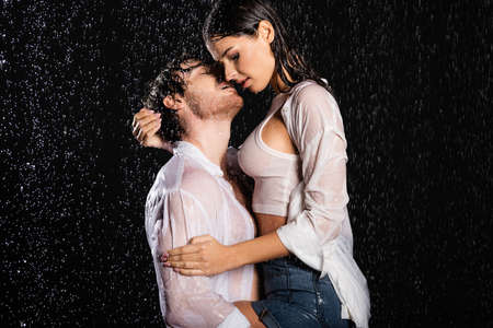 romantic couple in wet white shirts passionately hugging and kissing in rain drops on black background