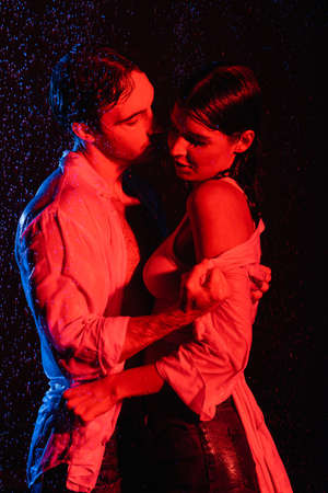 red and blue colors filters picture of wet romantic couple passionately hugging in water drops on black background Stock fotó
