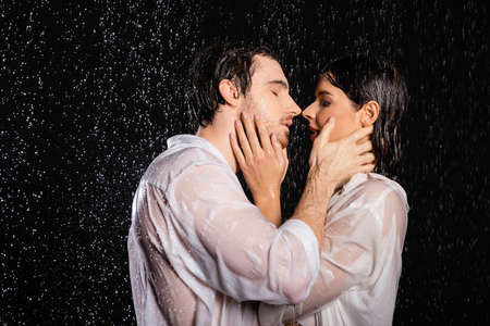 passionate couple in wet clothes standing in rain drops on black background