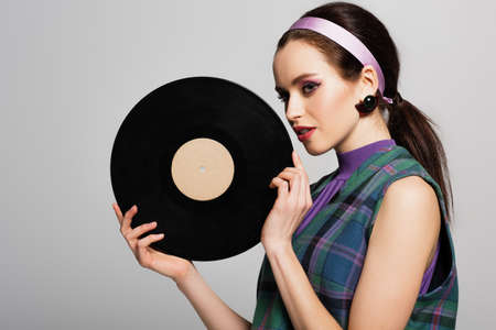 pretty young woman in headband holding retro vinyl disc isolated on gray Stock fotó