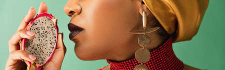 cropped view of young african american woman holding half cut of dragon fruit on green, banner