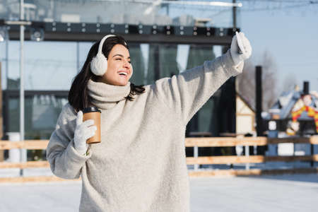 happy woman in sweater and ear muffs holding paper cup and taking selfie on ice rink Reklamní fotografie