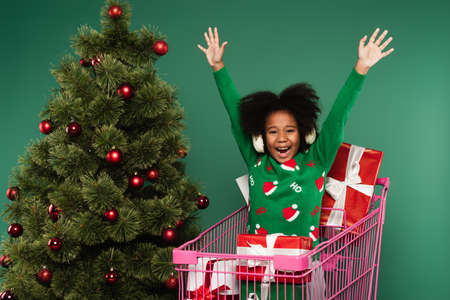 Excited african american girl in ear muffs sitting in shopping cart with presents near christmas tree isolated on green