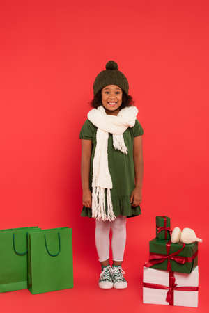 Happy african american kid in hat and scarf standing near shopping bags, presents and ear muffs on red background