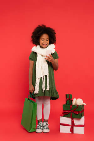 Happy african american child in scarf using smartphone and holding shopping bag near presents with ear muffs on red background