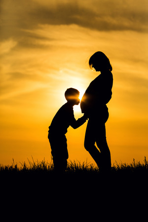 Silhouette pregnant woman and her son kissed Stock Photo
