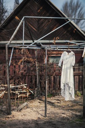 hanged woman: Wedding dress on a hanger in a village Stock Photo