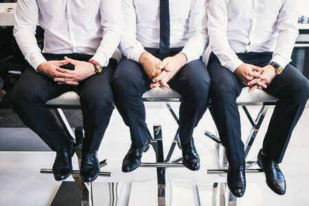 barstools: Three men in white shirts and trousers Stock Photo