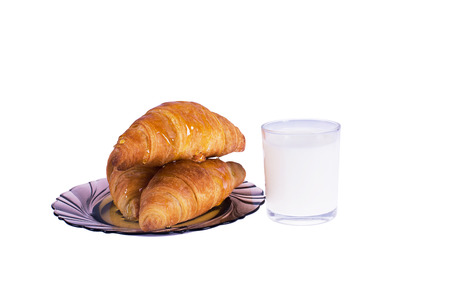 Croissants on a plate with milk isolated on white photo