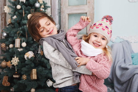 작은 소녀와 소년 크리스마스 트리 주위에 포옹