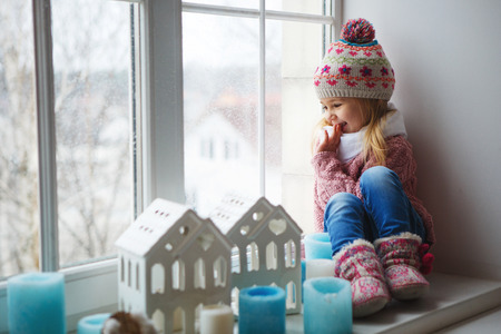 winter day: little girl on a window sill looks at the street