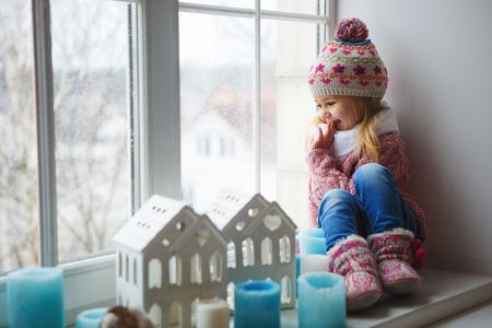 felicidade: menina em um peitoril da janela olha para a rua