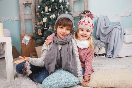 작은 소녀와 소년 크리스마스 트리 주위에 새 해 선물 스톡 콘텐츠