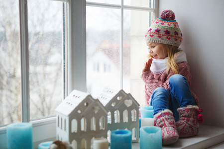 Little girl sitting on a window sill and looks at the street
