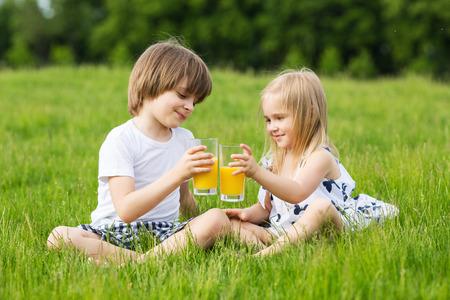 Little girl and boy outdoor summer drink juice