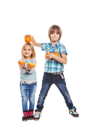 소년과 소녀 흰색 배경에 오렌지를 잡고있다 스톡 콘텐츠