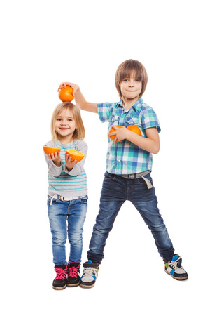 Boy and girl are holding oranges on a white background