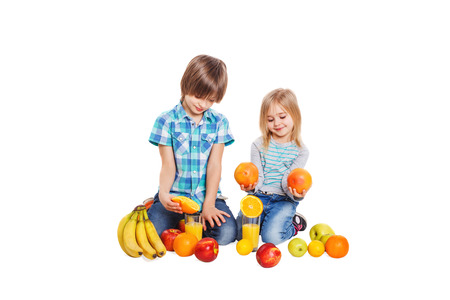 The boy and the girl on a white background and near them lies a lot of different fruit photo