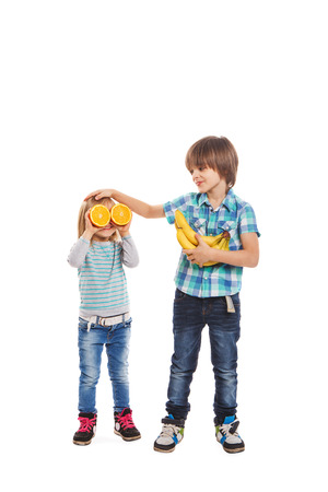 Boy and girl are holding oranges and bananas on a white background photo