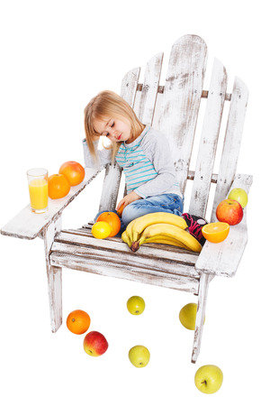 The little girl on wooden chairs and nearby is a lot of fruit photo