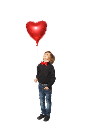 Boy on a white background in a black shirt with a bow tie holding a balloon in the shape of heart photo