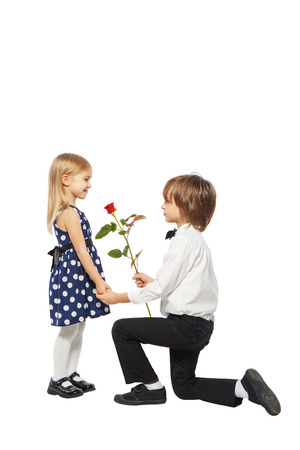 Boy on one knee gives a girl a rose on a white background photo